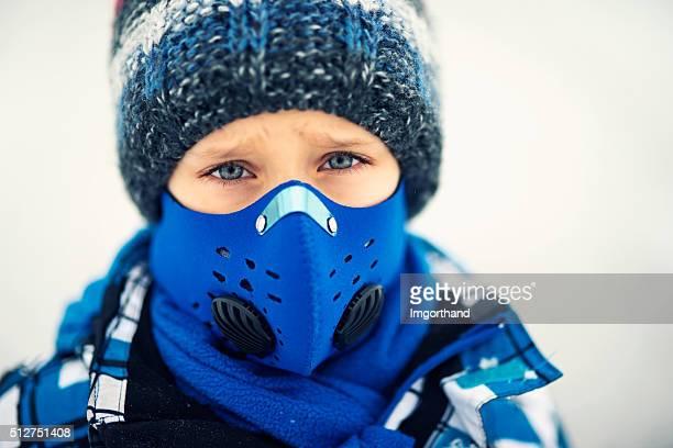 Portrait of little boy wearing modern pollution mask