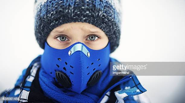 Portrait of little boy wearing modern pollution mask