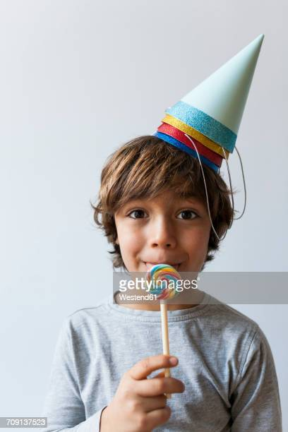 Portrait of little boy with lollipop and four party hats on his head