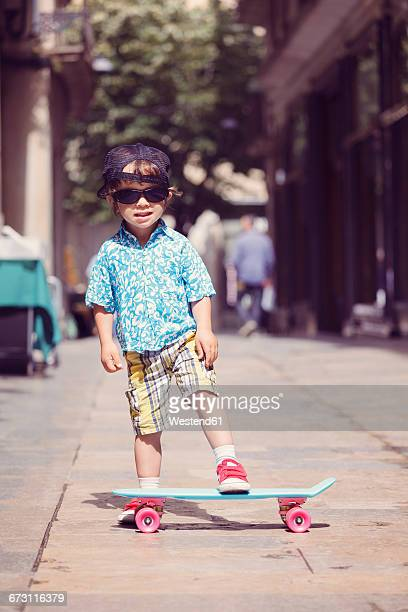 Portrait of little boy with skateboard wearing oversized sunglasses and basecap