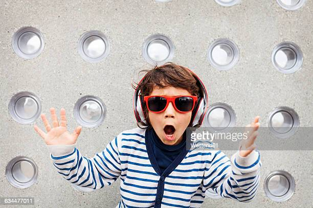 Portrait of little boy with sunglasses rapping while listening music with headphones