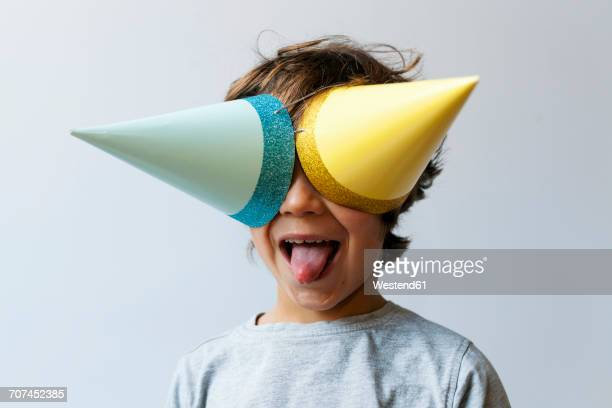portrait of little boy with two party hats on his eyes sticking out tongue - grimacing stock pictures, royalty-free photos & images