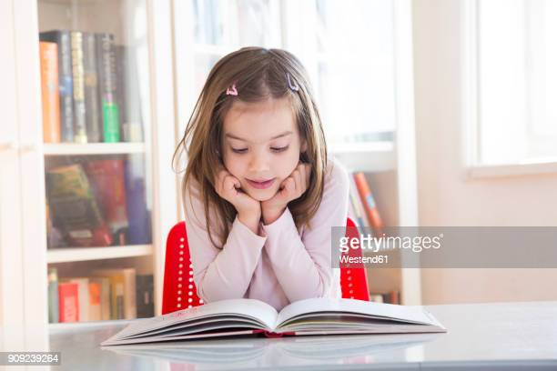 portrait of little girl at table reading a book - reading stock pictures, royalty-free photos & images