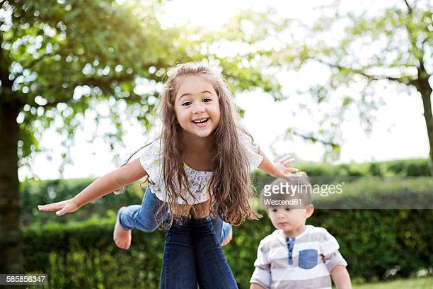 Portrait of little girl balancing on her mothers knee
