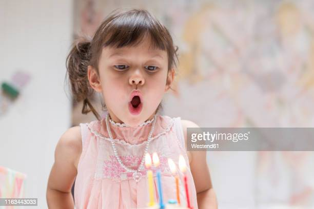 portrait of little girl blowing out burning candles on her birthday cake - soplar fotografías e imágenes de stock