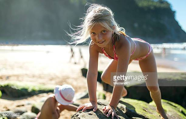 Portrait of little girl climbing on a rock at the beach