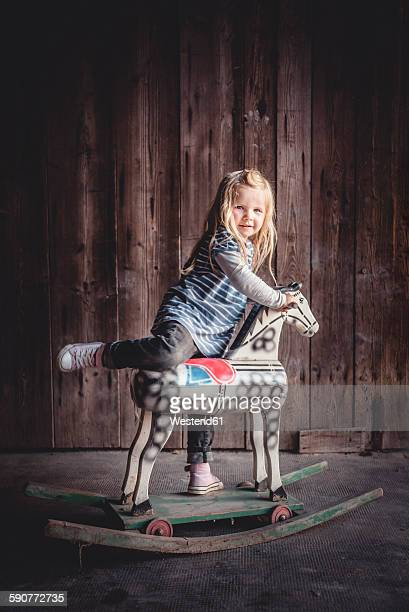 Portrait of little girl climbing on a vintage rocking horse in a barn