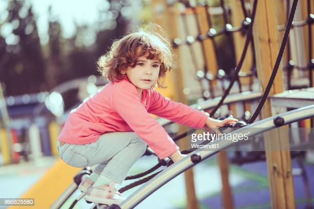 Portrait of little girl crouching on climbing frame at playground