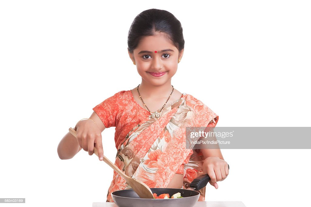 Portrait of little girl dressed as housewife cooking : Stock Photo