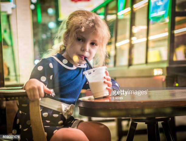 Portrait of little girl drinking delicious milkshake from straw in cafe