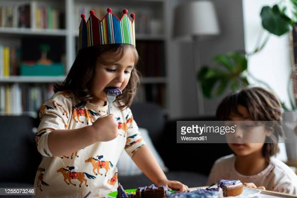 portrait of little girl eating birthday cake - happy birthday images for sister stock pictures, royalty-free photos & images