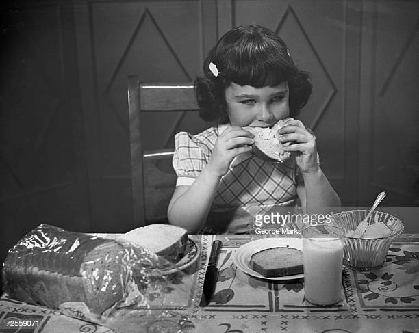 Portrait of little girl eating buttered toast