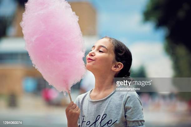 portrait of little girl eating cotton candy - traveling carnival stock pictures, royalty-free photos & images
