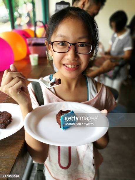 Portrait Of Little Girl Having Cake At Party
