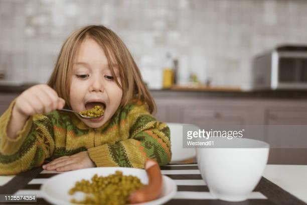 portrait of little girl having lunch in the kitchen - hungrig stock-fotos und bilder