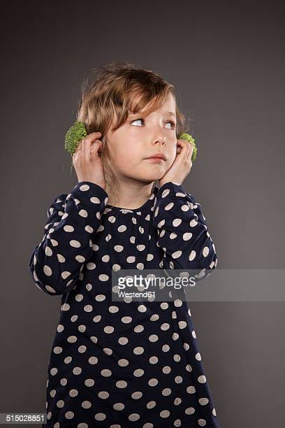 Portrait of little girl holding broccoli on his ears