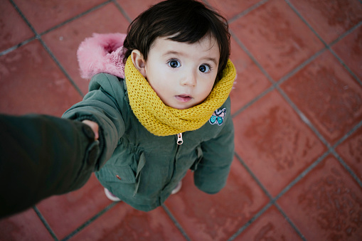 Portrait of little girl holding mother's hand looking up - gettyimageskorea