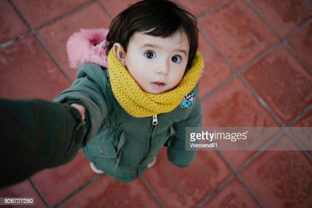 portrait of little girl holding mother's hand looking up - chiedere foto e immagini stock