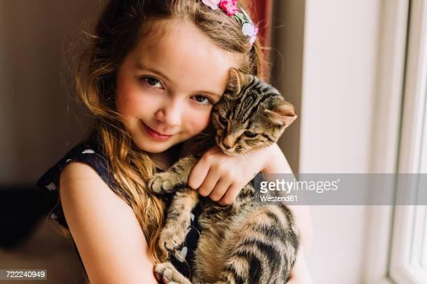 Portrait of little girl holding tabby kitten