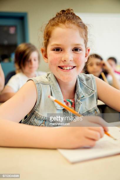Portrait of little girl in classroom, sitting at her desk.