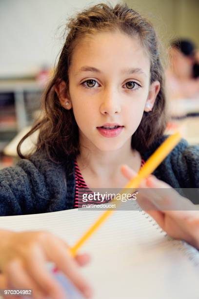 """portrait of little girl in classroom, sitting at her desk. - """"martine doucet"""" or martinedoucet stock pictures, royalty-free photos & images"""