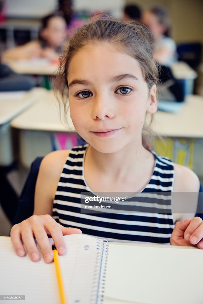 Portrait of little girl in classroom, sitting at her desk. : Stock Photo