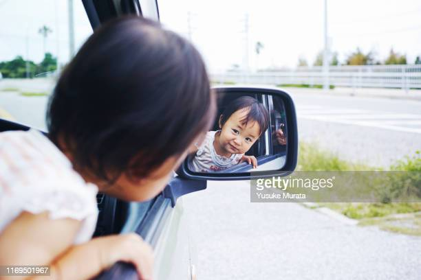 portrait of little girl in side-view mirror of car - 列車の車両 ストックフォトと画像