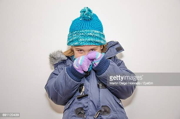 Portrait Of Little Girl In Warm Clothes Hiding Face Against White Background