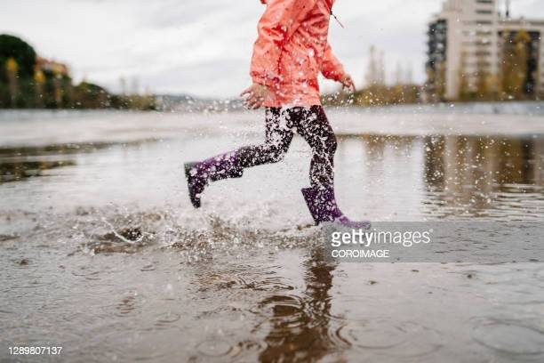 portrait of little girl jumping on a rain puddle on cloudy day - silver boot stock pictures, royalty-free photos & images