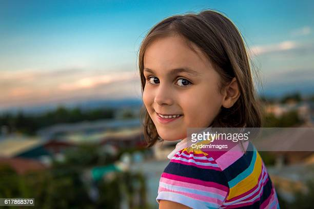 Portrait of little girl looking at camera with content smile