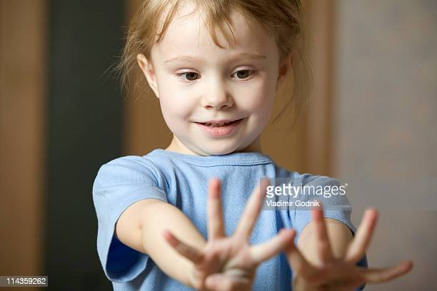 portrait of little girl looking at her hands