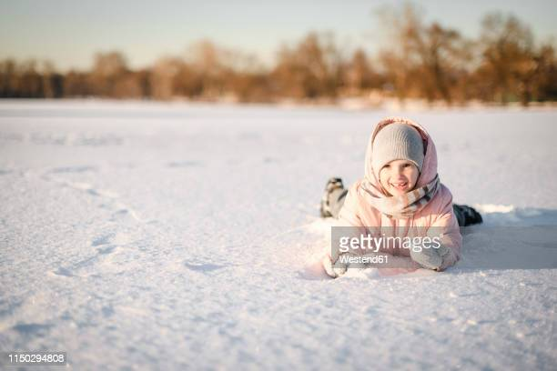 portrait of little girl lying in snow field - snowfield stock pictures, royalty-free photos & images