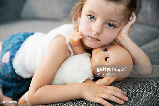 Portrait of little girl lying on sofa with her doll, close-up