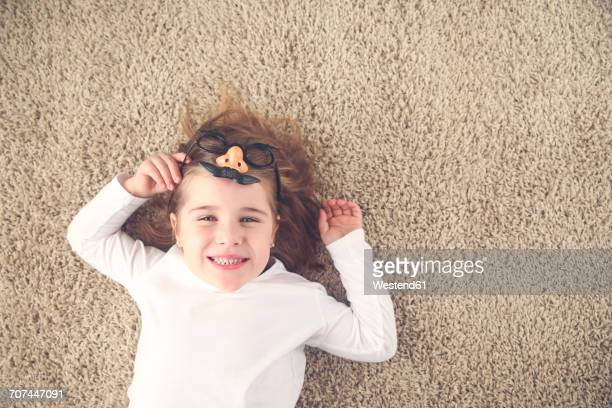 Portrait of little girl lying on the carpet holding funny glasses with plastic nose
