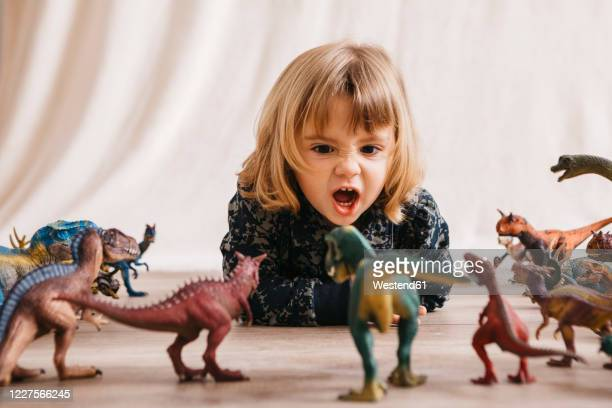 portrait of little girl lying on the floor playing with toy dinosaurs - dinosaur stock pictures, royalty-free photos & images