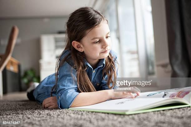 portrait of little girl lying on the floor watching picture book - 6 7 jahre stock-fotos und bilder