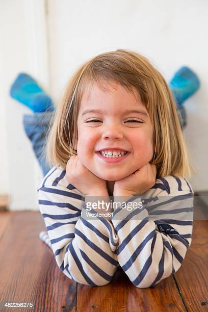 Portrait of little girl lying on wooden floor