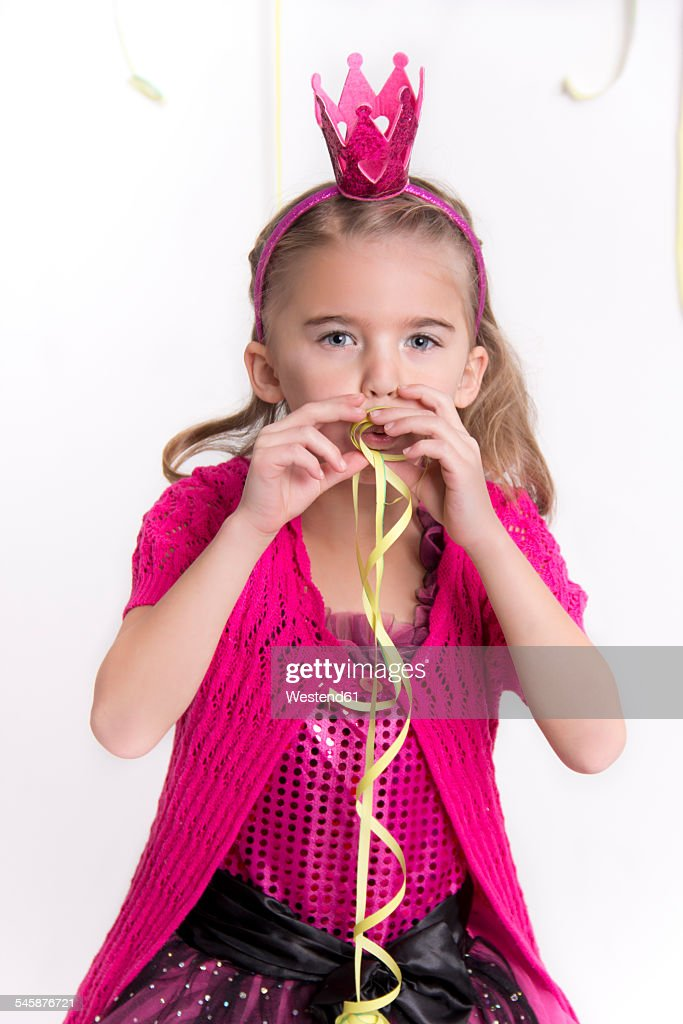 Portrait Of Little Girl Masquerade As A Princess Blowing Streamer