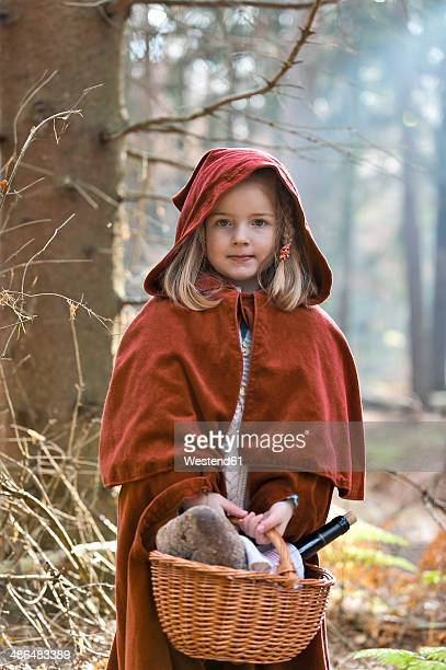 portrait of little girl masquerade as red riding hood standing in the wood - le petit chaperon rouge photos et images de collection