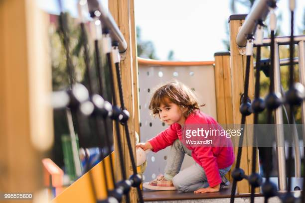 Portrait of little girl on climbing frame at playground