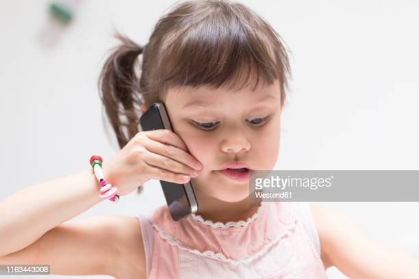 portrait of little girl on the phone looking down - 4 5 jahre stock-fotos und bilder