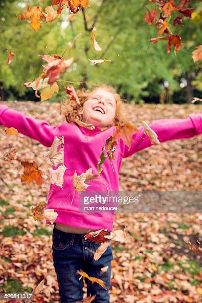 "portrait of little girl playing with autumn fallen leaves. - ""martine doucet"" or martinedoucet stockfoto's en -beelden"