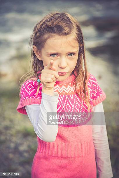 Portrait of little girl pointing at viewer