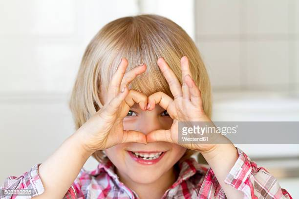 Portrait of little girl shaping heart with fingers
