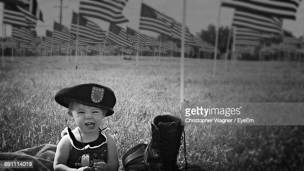 Portrait Of Little Girl Siting Against American Flags On Field