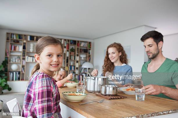 Portrait of little girl sitting at dining table with her parents and sister