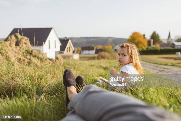 portrait of little girl sitting on a meadow with a book looking at her mother - ponto de vista - fotografias e filmes do acervo