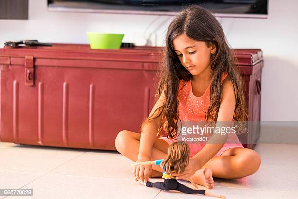portrait of little girl sitting on the floor playing with doll - girl chest stock photos and pictures