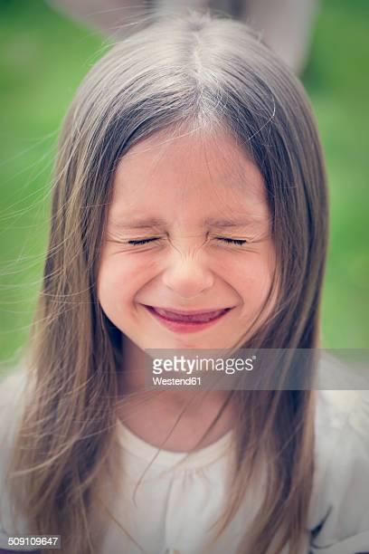 Portrait of little girl squinting eyes
