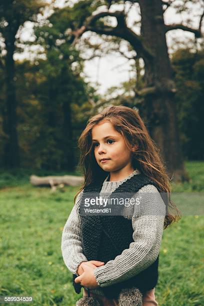 Portrait of little girl standing in an autumnal park